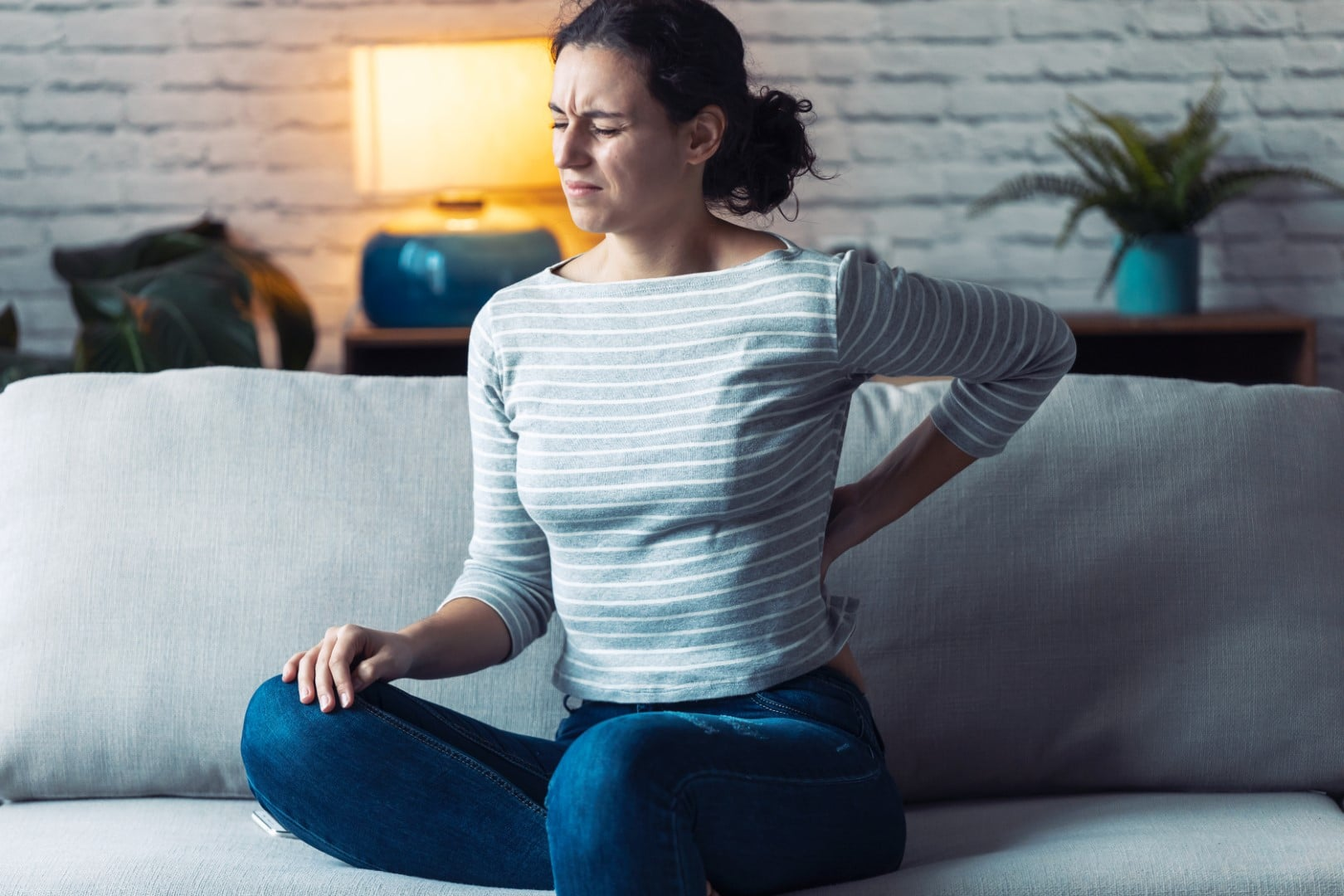 Young woman with back pain sitting on the sofa in the living room